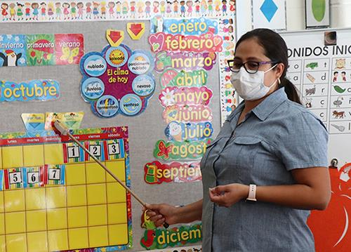photo of teacher pointing to bulletin board
